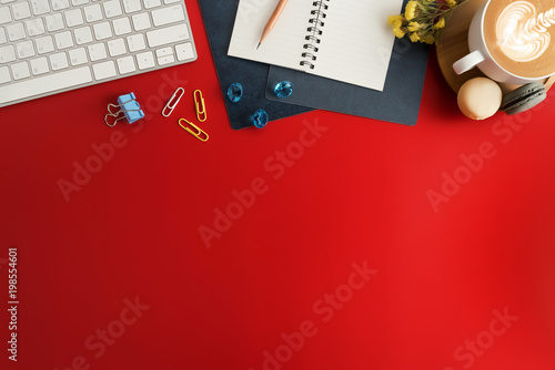 plakat Styled stock photography red office desk table with blank notebook, keyboard, macaroon, supplies and coffee cup. Top view with copy space. Flat lay.