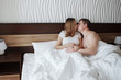 Young beautiful husband and wife resting in bed under a white blanket in a hotel room