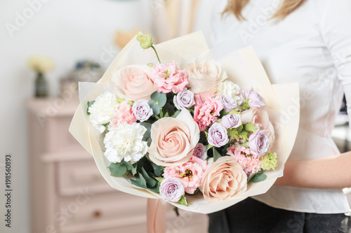 beautiful luxury bouquet of mixed flowers in woman hand. the work of the florist at a flower shop. A small family business © malkovkosta
