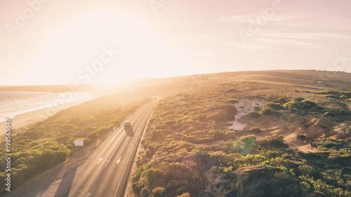 Aerial View of Car Driving Down Great Ocean Road, Australia at Sunset