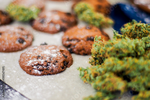 Fototapeta Cookies with cannabis and buds of marijuana on the table. Concept of cooking with cannabis herb. Treatment of medical marijuana for use in food On a white background obraz