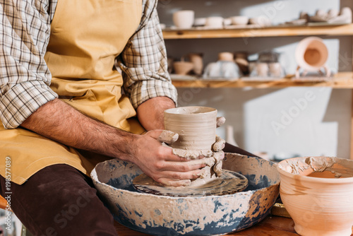 Papiers peints Jardin partial view of male hands with ceramic pot on pottery wheel