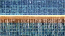Water Flows Over The Edge Of The Swimming Pool From The Blue Tiles