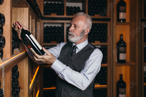 Mature sommelier choosing a bottle of wine at the wine cellar.