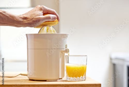 Hand pressing orange fruit with electric juicer