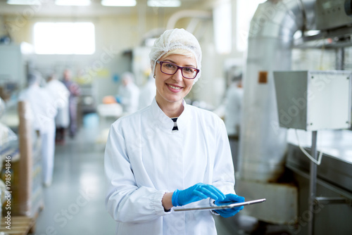Young joyful beautiful female worker in sterile cloths holding a tablet and smiling for the camera near factory production line.