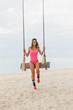 young woman in pink swimsuit sitting on swing on beach at resort