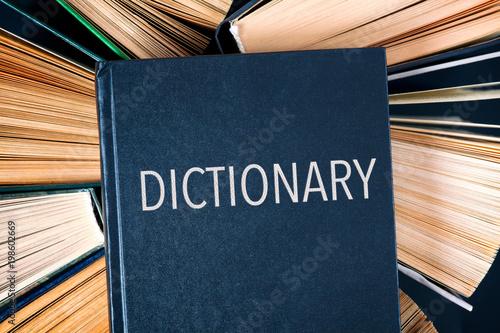 Fotografia, Obraz  Old hardback books with book Dictionary on top.