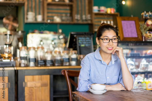Foto op Plexiglas Bakkerij Smiling intelligent girl waiting for order in cafe. Cheerful dreamy attractive young Asian woman enjoying weekend time. Leisure concept