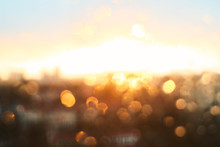 Rain Drops Texture On Window Glass With Gorgeous Vintage Orange Amber Sunset Light Abstract Blurred Cityscape Skyline Bokeh Background. Soft Focus.