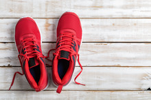Red Running Shoe On White Wood...