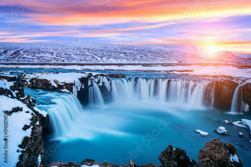 Cascade Godafoss waterfall at sunset in winter, Iceland.