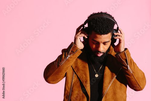 Fotografia  Cool African American man with beard holding headphones and looking down, isolat