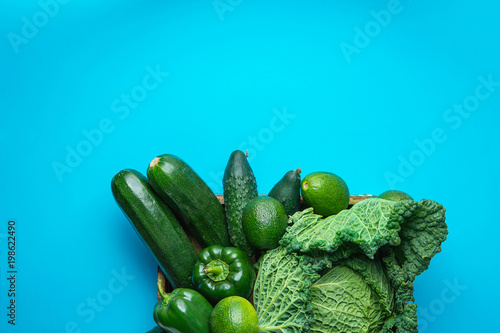 Tray with Fresh Organic Green Vegetables Savoy Cabbage Zucchini Cucumbers Bell Peppers Avocados on Bright Blue Background. Superfoods Vegan Plant Based Diet Concept. Copy Space