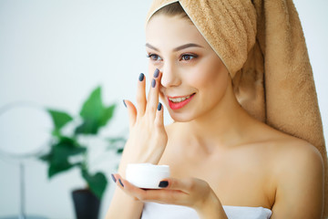 A beautiful woman using a skin care product, moisturizer or lotion and Skincare taking care of her dry complexion. Moisturizing cream in female hands