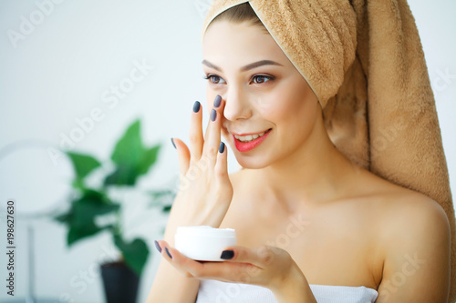 Fotografia A beautiful woman using a skin care product, moisturizer or lotion and Skincare taking care of her dry complexion