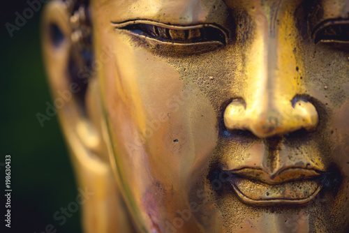 close up of a golden colored buddha head on black background ; China Fototapete