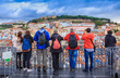 Group of tourists watching the cityscape of Lisbon and taking pictures of Sao Jorge castle in Portugal