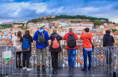 Fototapeta Group of tourists watching the cityscape of Lisbon and taking pictures to Sao Jorge castle in Portugal obraz