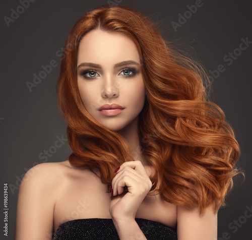 Beautiful model girl with long red curly hair .Red head . Care and beauty hair products