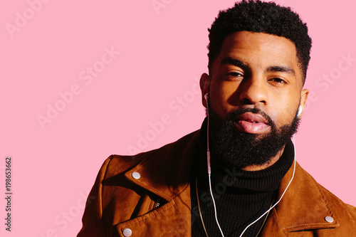 Foto Portrait of a cool man with beard and headphones isolated on pink studio backgro
