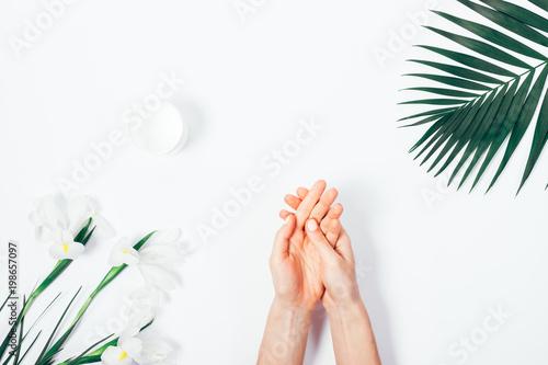 Fotografía  Woman applying hand cream among tropical flowers