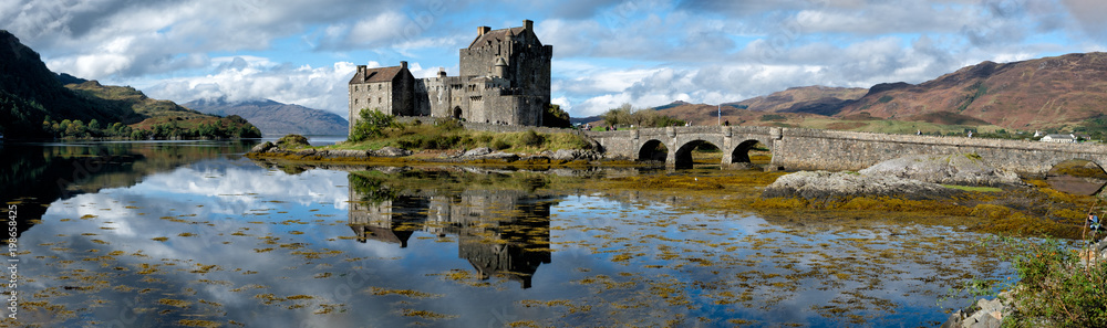 Fototapeta A panorama of the Eilean Donan Castle on a sunny afternoon in Scotland.