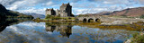 A panorama of the Eilean Donan Castle on a sunny afternoon in Scotland.