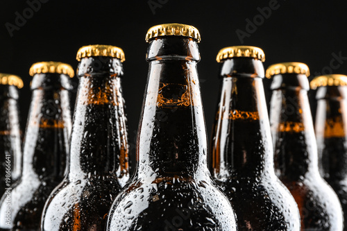 Fényképezés  Glass bottles of beer on black background, closeup