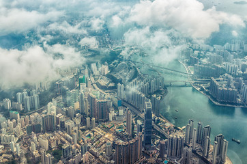 Bird's eye or aerial view through the clouds to large metropolis city of Hong Kong.