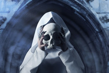A Woman In White Hooded Cloak Holding A Human Skull In Front Of Her Face On Temple Arch Background.