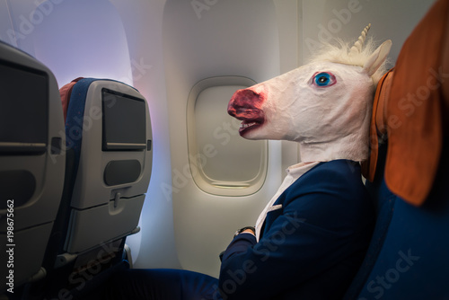 Foto Unusual passenger in elegant suit sits alone inside the aircraft and ready to departure