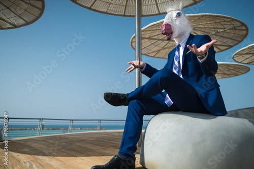 Young businessman in suit sits under umbrellas on the city waterfront and spreads his hands Slika na platnu