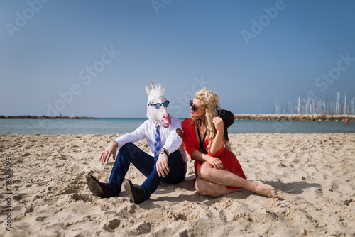 Foto op Aluminium Ontspanning Young man in suit sits with trendy woman on the beach. Unusual guy in funny mask and sunglasses with girlfriend. Freaky unicorn relaxes with beautiful girl on the background of sea and sky