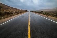 Empty Wet Desert Asphalt Pavement Road With Yellow Highway Marking Lines.