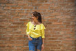 Portrait smile asian girl in yellow dress and jeans beside brick wall