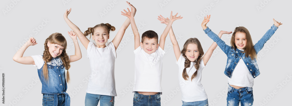 Fototapeta Group happy children  friends with their hands up on a white background