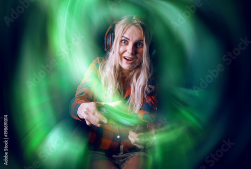 girl gamer in headphones and with a joystick in her hands playing network games Poster