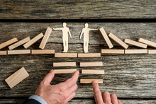 Conceptual Of Teamwork With Two Businessmen Offering Support To A Paper Men