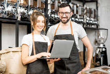 Coffee Store Owners Or Managers Working With Laptop Standing At The Counter Of The Shop