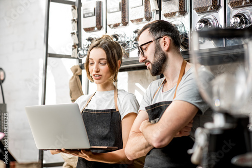 Photo Coffee store owners or managers working with laptop standing at the counter of t