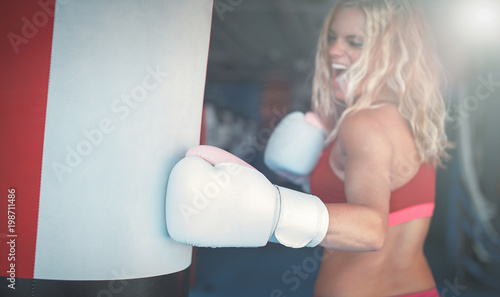 Photo  Young woman punching into heavy bag in gym cinematic style
