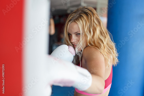 Young blonde woman punching into heavy bag in gym Wallpaper Mural