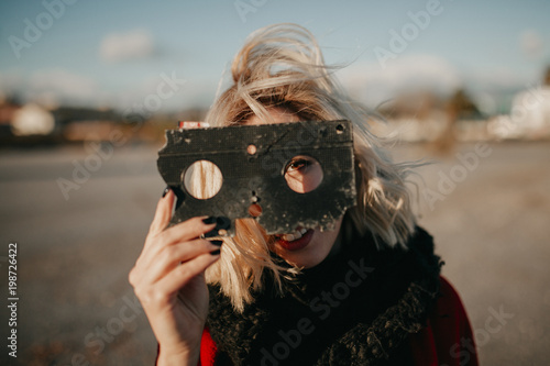 Fotografie, Obraz  Blonde alternative woman playing with a VHS tape outdoors at sunset