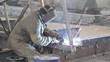 Worker welds metal structures in the factory