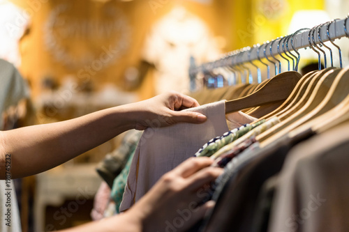 Obraz Close up of woman hand choosing thrift young and discount t-shirt clothes in store, searching or buying cheap cotton shirt on rack hanger at flea market , stall shopping apparel fashion concept - fototapety do salonu