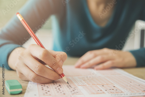 Fotografia  Female student holding pencil and examination paper