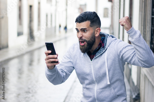 Enthusiastic young man looking at cellphone with victorious expression in the city Fotobehang