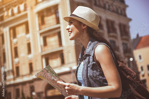 Side view outgoing female exploring city while looking at map. Happy tourist during trip concept