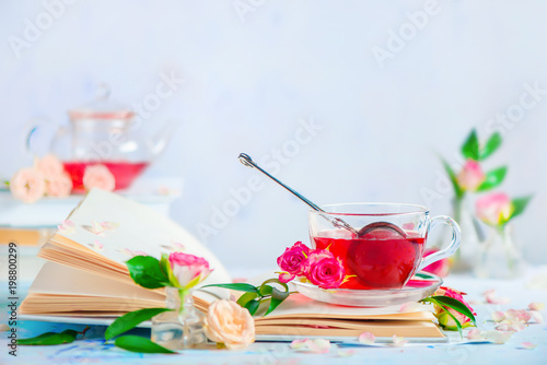 Cup of rose petals tea on an open book on a white background with